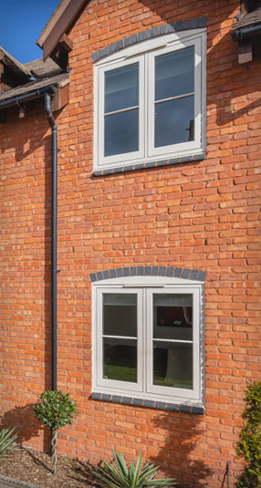 Close up of Chartwell Green casement windows on red bricked wall