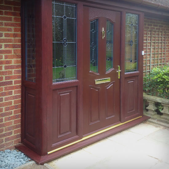 Brown Dark Wood composite door in matching porch surround with lead linned effect on the glass